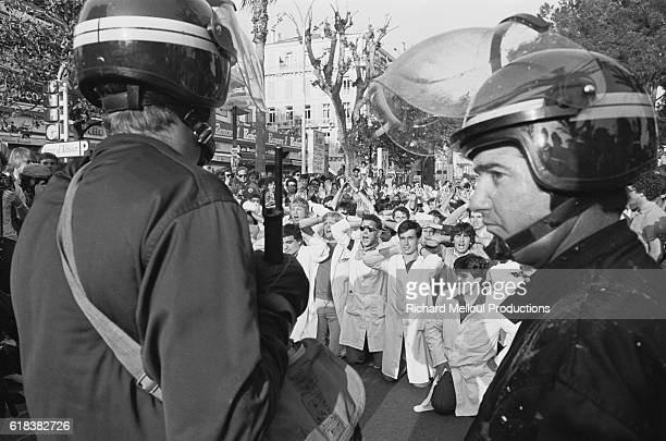 Riot police keep an eye on a crowd of medical students staging a protest in front of the Palais des Festivals in Cannes France