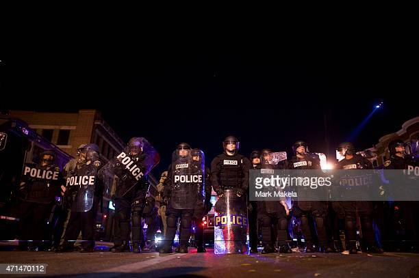 Riot police line the street in advance of curfew the night after citywide riots over the death of Freddie Gray on April 28, 2015 in Baltimore,...