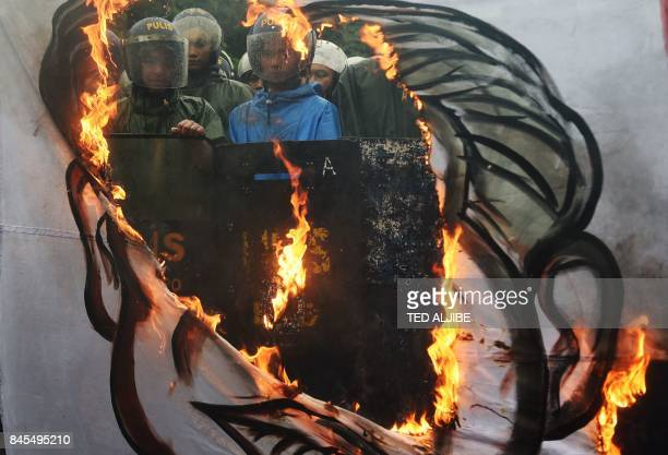 TOPSHOT Riot police look on past a burning banner with a representation of a composite portrait of late dictator Ferdinand Marcos and President...