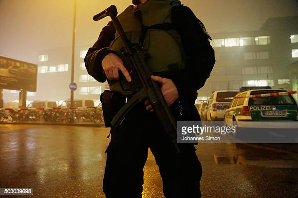 A riot police man armed with a machine gun controls the street in front of Pasing railway station on January 1 2016 in Munich Germany According to...