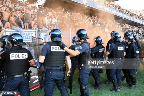 Riot police members stand guard to prevent supporters from invading the pitch during the French L1 football match between Montpellier and Nimes on...
