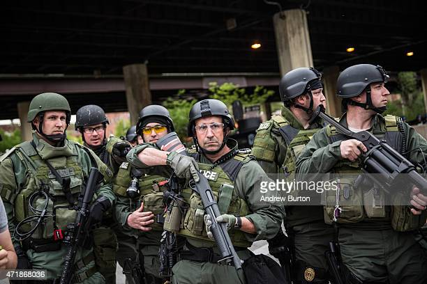 Riot police monitor protesters during a march in support of Maryland state attorney Marilyn Mosby's announcement that charges would be filed against...