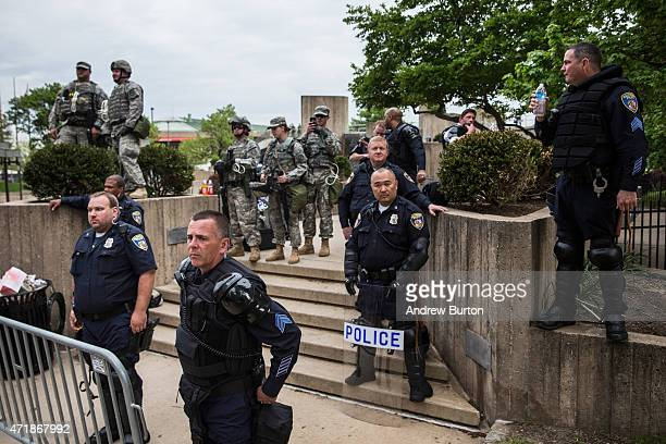 Riot police monitor protesters march through the streets in support of Maryland state attorney Marilyn Mosby's announcement that charges would be...