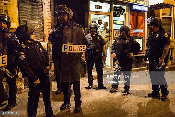 Riot police monitor protesters near a CVS pharmacy that was looted and burned by rioters on Monday after the funeral of Freddie Gray, on April 29,...