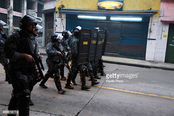 Riot police move through a street after an eviction ended in violent clashes in downtown Sao Paulo The eviction occurred in a building that was...