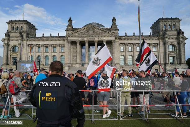 Riot police observe far-right protesters gathered outside the Reichstag during protests against coronavirus-related restrictions and government...