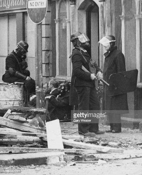 Riot police of the Royal Ulster Constabulary resting as their colleague prepares to fire a tear gas gun after violence flared on the streets of...