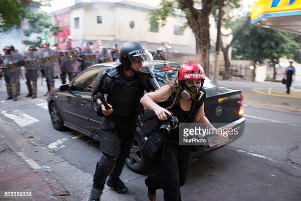 Riot police officer attacks a photojournalist during a protest against an increase in subway, trains and bus fares in Sao Paulo, Brazil on January 9,...