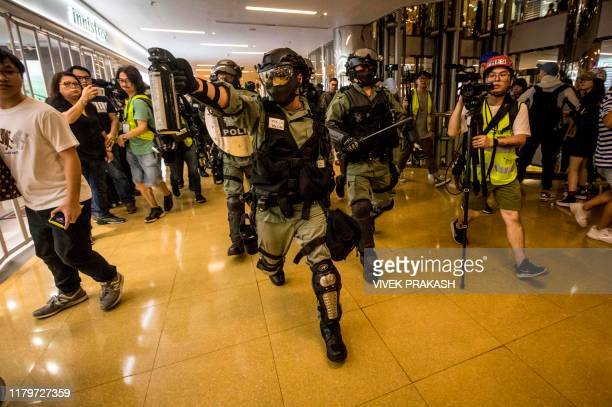 A riot police officer chases a protester while wielding a can of pepper spray inside the City Plaza mall in the Tai Koo Shing area in Hong Kong on...