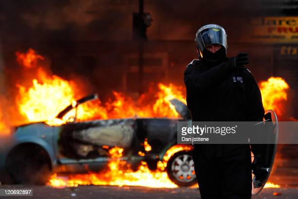 A riot police officer directs his colleagues to clear people away from a burning car in Clarence Road in Hackney on August 8 2011 in London England...