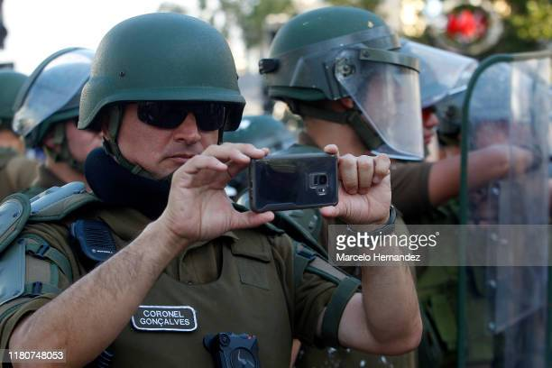 A riot police officer film with his phone during a protest against the government of president Sebastian Piñera on November 7 2019 in Santiago Chile...