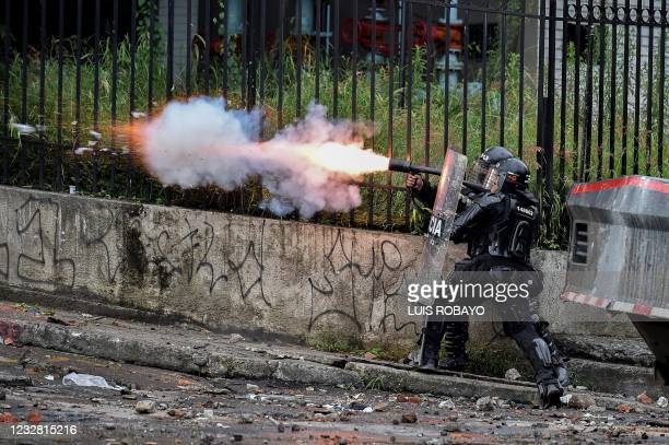 Riot police officer fires tear gas at demonstrators during a protest against the government in Cali, Colombia, on May 10, 2021. - Faced with angry...
