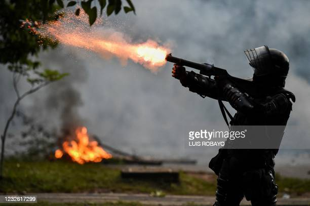Riot police officer fires tear gas at demonstrators during clashes following a protest against a tax reform bill launched by President Ivan Duque, in...