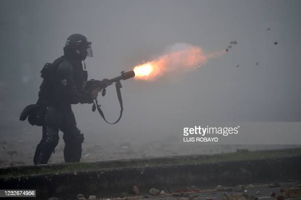 Riot police officer fires tear gas at demonstrators during clashes to protest against a tax reform bill launched by President Ivan Duque, despite the...