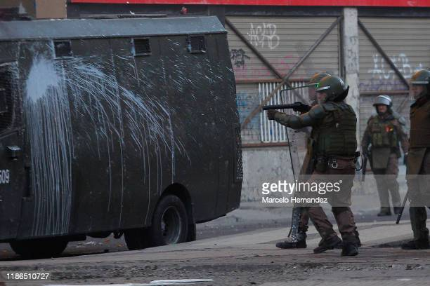 Riot police officer fires to demonstrators during protests against president Piñera at Plaza Italia on December 4, 2019 in Santiago, Chile. Today...
