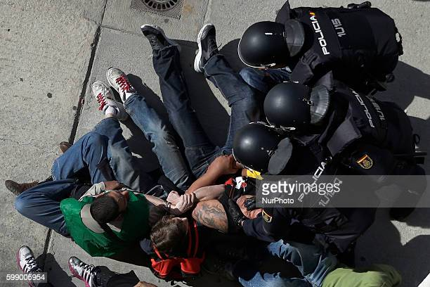 A riot police officer grabs the face of a member of the Victims' Mortgage Platform as he tries to block the door of Veronica Carro to prevent her...