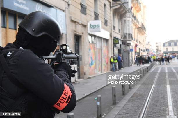 A riot police officer holds a 40millimetre rubber defensive bullet launcher LBD weapon during an antigovernment demonstration called by the Yellow...