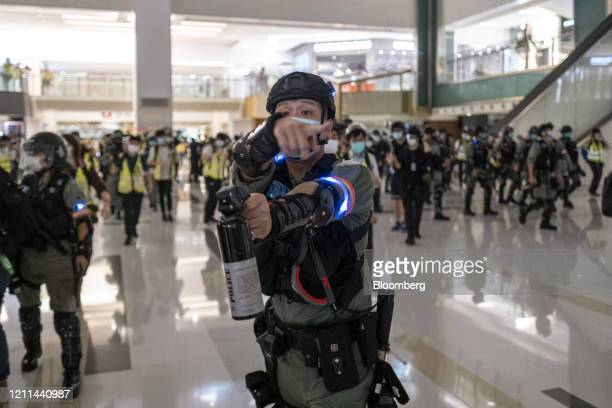 A riot police officer holds a pepper spray aerosol as crowds are dispersed during a protest inside the New Town Plaza shopping mall in the Shatin...