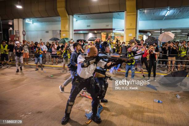 A riot police officer holds a shotgun towards protestors during a demonstration on July 30 2019 in Hong Kong China Protesters have continued weekly...