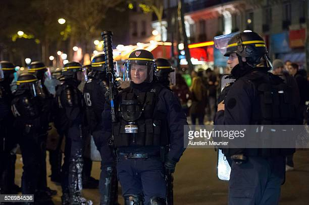 A riot police officer holds a tear gas launcher as they secure Place de le Republique after protestors listened to speeches during the 'Nuit Debout'...