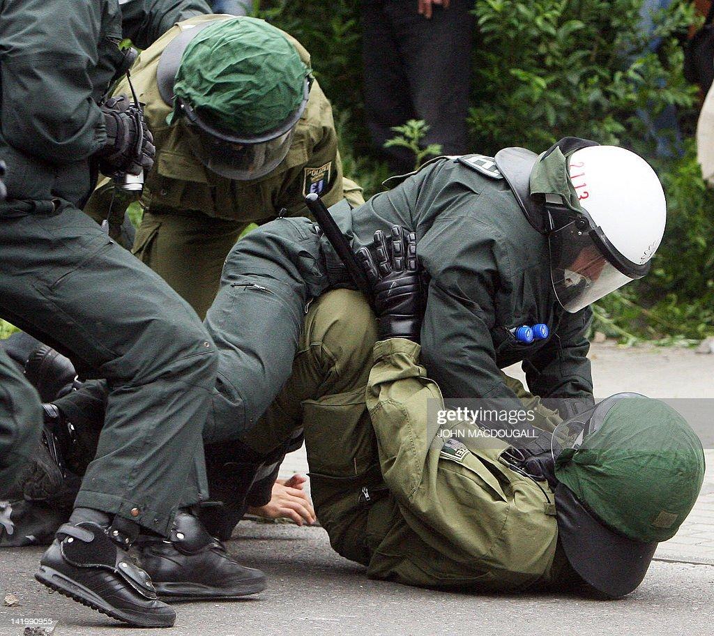 A riot police officer holds down a colle : Foto jornalística