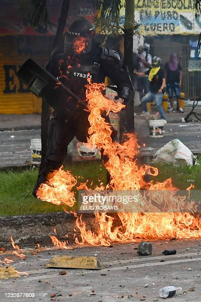 Riot police officer is hit by a Molotov cocktail during clashes with riot police officers during a protest against a proposed government tax reform...
