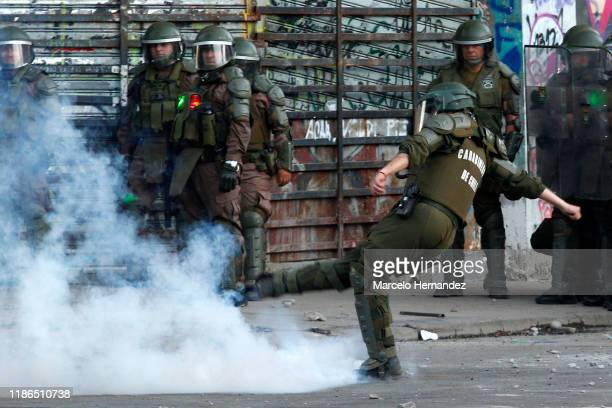 Riot police officer kicks a gas bomb during protests against president Piñera at Plaza Italia on December 4, 2019 in Santiago, Chile. Today deputies...