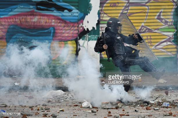 Riot police officer kicks a tear gas canister at demonstrators during a protest against a proposed government tax reform in Cali, Colombia, on May 3,...