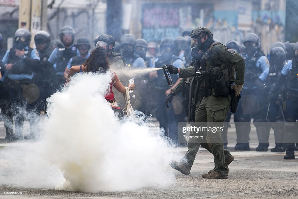 A riot police officer pepper-sprays a demonstrator during a protest against austerity measures in Hato Rey neighborhood of San Juan, Puerto Rico, on Tuesday, May 1, 2018. Puerto Rico demonstrators battled police on San Juan's streets as they marched against proposed cuts to retirement benefits and looser labor laws as the bankrupt island seeks to reduce $74 billion of debt. Photographer: Xavier Garcia/Bloomberg via Getty Images
