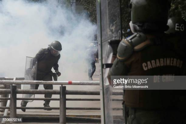 A riot police officer runs away from the tear gas during protests against the government of Sebastián Piñera on its second anniversary on March 11...