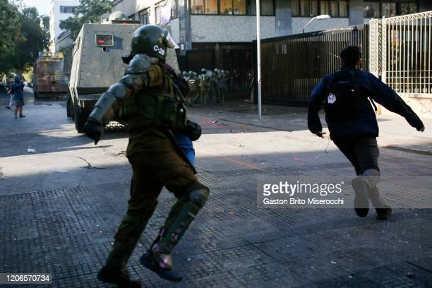 A riot police officer runs behind a demonstrator during protests against the government of Sebastián Piñera on its second anniversary on March 11...
