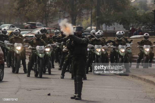 A riot police officer shoots tear gas during protests against the government of Sebastián Piñera on its second anniversary on March 11 2020 in...