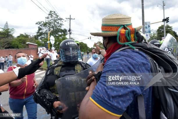 Riot police officer stands between indigenous people and citizens who oppose blockades set by demonstrators during protests triggered by a now...