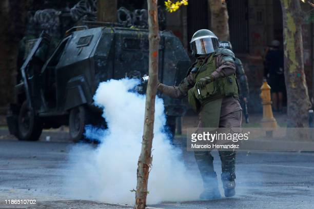 Riot police officer throws a gas canister to demonstrators during protests against president Piñera at Plaza Italia ona on December 4, 2019 in...