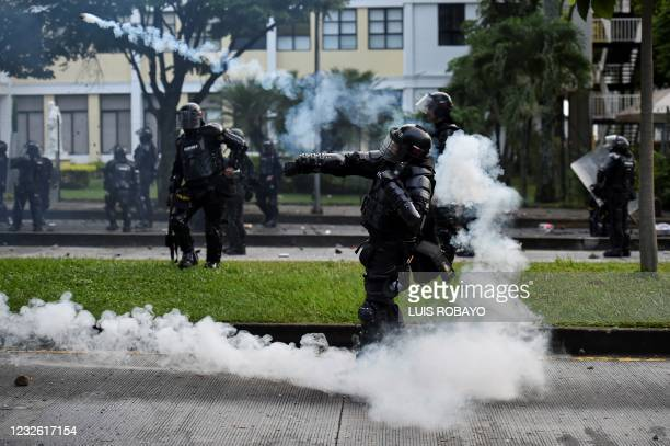 Riot police officer throws a tear gas canister at demonstrators during clashes following a protest against a tax reform bill launched by President...