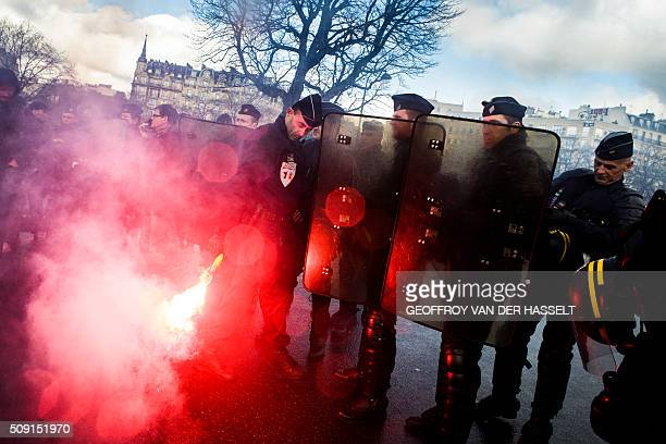 A riot police officer throws back a burning flare on the Place de la Nation in Paris on February 9 during a demonstration by nonlicensed private hire...