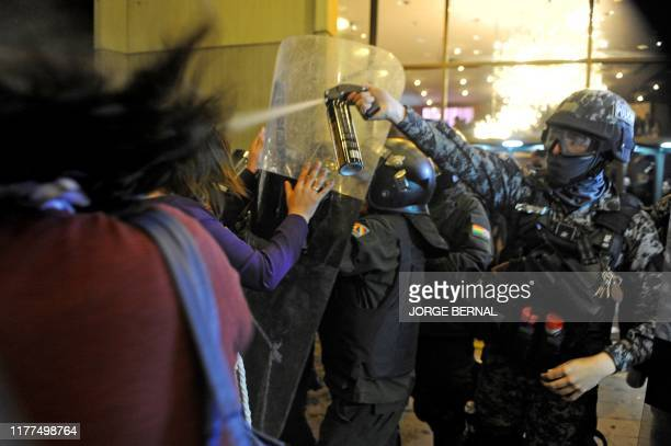 TOPSHOT A riot police officer throws pepper spray at supporters of Bolivia's main opposition presidential candidate former president Carlos Mesa...