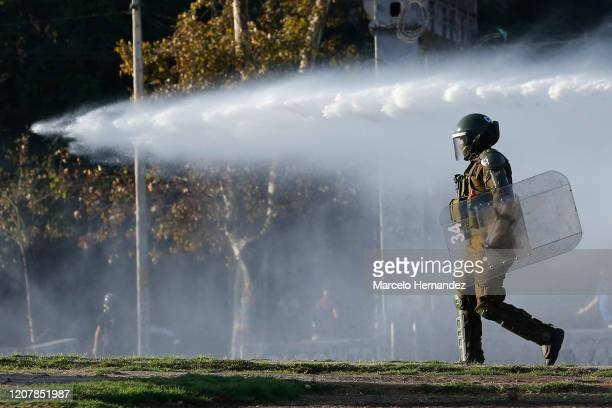 Riot police officer walks as a water cannon fires behind during a protest against the government of President Sebastian Piñera on March 20, 2020 in...