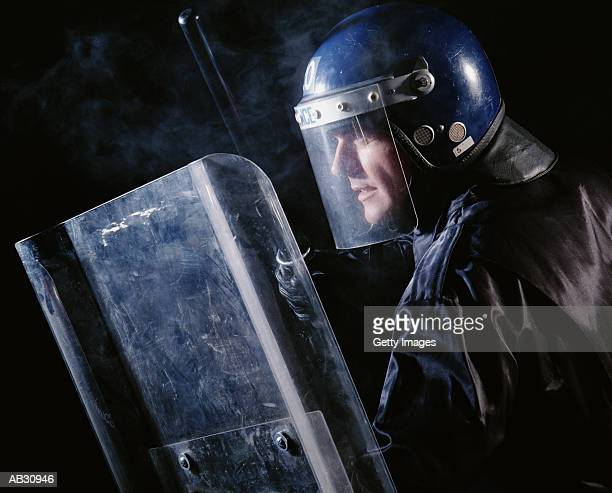 Riot police officer with helmet, shield and baton