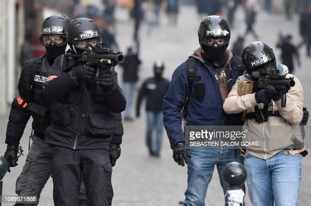 TOPSHOT Riot police officers aim at protesters with rubber bullets less lethal gun during an antigovernment demonstration called by the Yellow Vests...