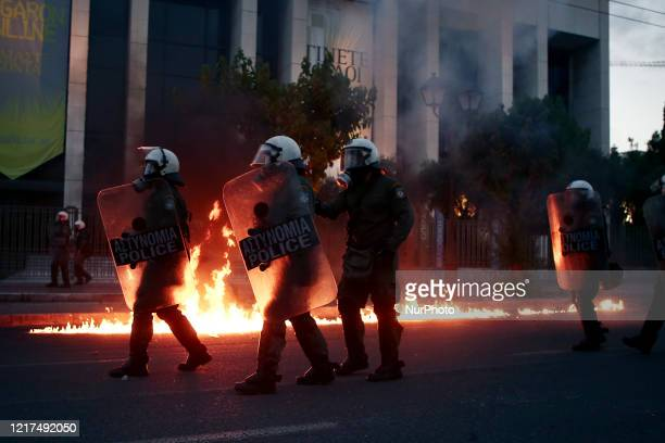 Riot police officers amid flames by petrol bombs thrown by protesters close to the US embassy during a demonstration over the death of George Floyd...