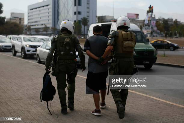 Riot police officers arrest a demonstrator during protests against the government of Sebastián Piñera on its second anniversary on March 11 2020 in...