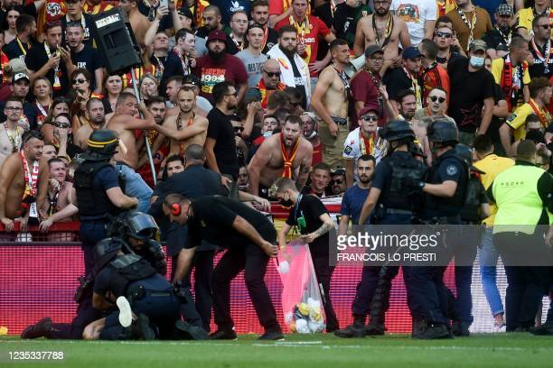 Riot police officers arrest a man after Lens' supporters invade the pitch during the French L1 football match between RC Lens and Lille at Stade...