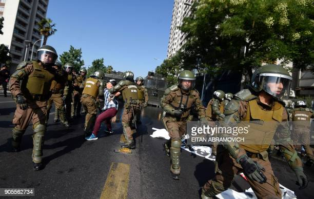 Riot police officers arrest a protester during a demonstration against the visit of Pope Francis to Chile in the surroundings of O'Higgins Park in...