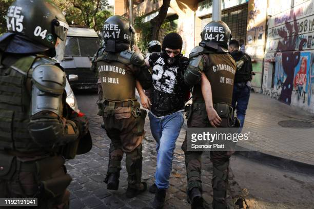 Riot police officers arrest a protester in downtown Santiago as demonstrations continue against Chilean President Sebastian Piñera on December 05...