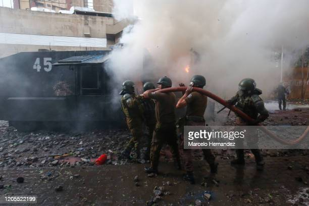 Riot police officers attempt to extinguish a fire of a water cannon truck during a protest against the government of president Sebastian Piñera on...