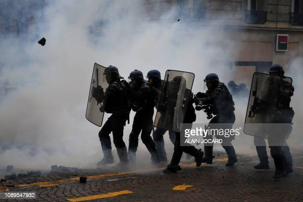 TOPSHOT Riot police officers clash amid smoke with protesters during an antigovernment demonstration called by the Yellow Vests Gilets Jaunes...
