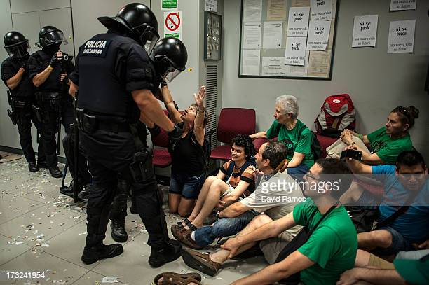 Riot Police officers clear the Banco Popular bank branch after being occupied by activist of the platform for Mortgage Victims for 14 hours on July...