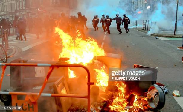Riot police officers cross a street next to burning trash cans during a yellow vest antigovernment demonstration in Lille northern France on January...