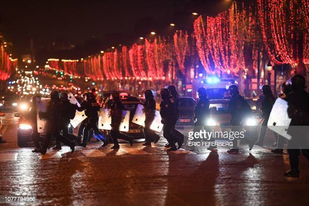 TOPSHOT Riot police officers cross the ChampsElysees avenue in Paris on January 5 2019 during an antigovernment demonstration called by the yellow...